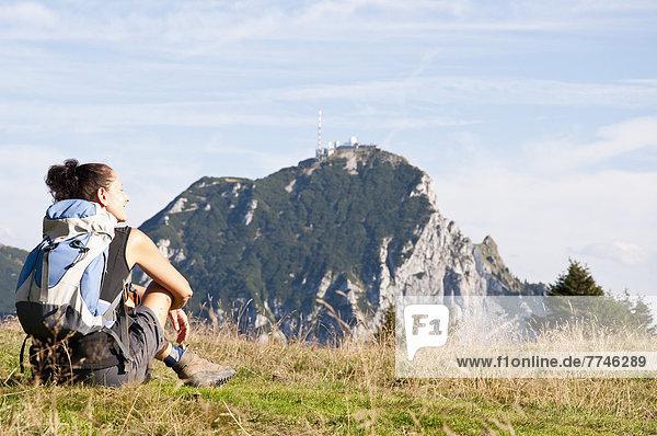 Mittlere erwachsene Frau sitzt auf der Wiese und schaut zu Wendelstein.