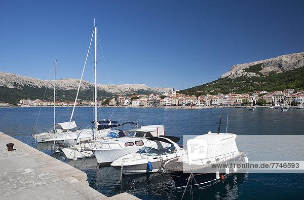 Kroatien  Boot liegt im Hafen auf der Insel Krk mit der Stadt Baska im Hintergrund.
