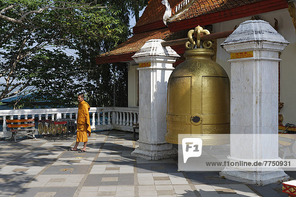 Large bell with a Buddhist monk in the temple complex of Wat Phra That Doi Suthep Ratcha Woraviharn