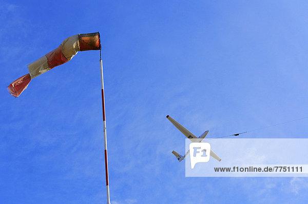 Windsack und Segelflugzeug im Windenstart gegen den Wind