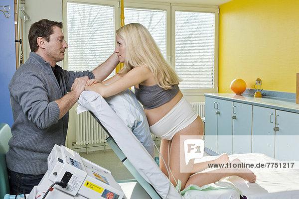 Mann und Frau im Kreißsaal während der Entbindung  die Frau kniet auf dem Entbindungsbett  ist an einen Wehenschreiber oder CTG angeschlossen  die beiden sehen sich liebevoll an