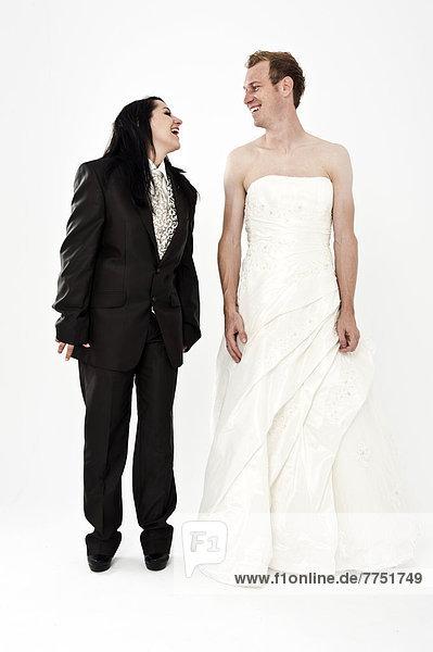 Braut in Anzug und Bräutigam in Hochzeitskleid lachen sich an  Kleidertausch  Hochzeit Braut in Anzug und Bräutigam in Hochzeitskleid lachen sich an, Kleidertausch, Hochzeit