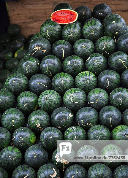 Gestapelte Wassermelonen (Citrullus lanatus) mit einer aufgeschnittenen halben Melone