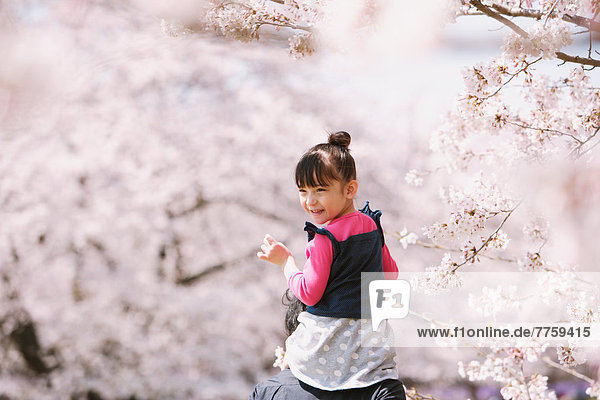 Father and daughter between cherry trees