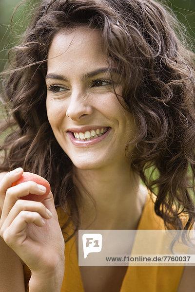 Porträt einer jungen Frau mit einer Aprikose