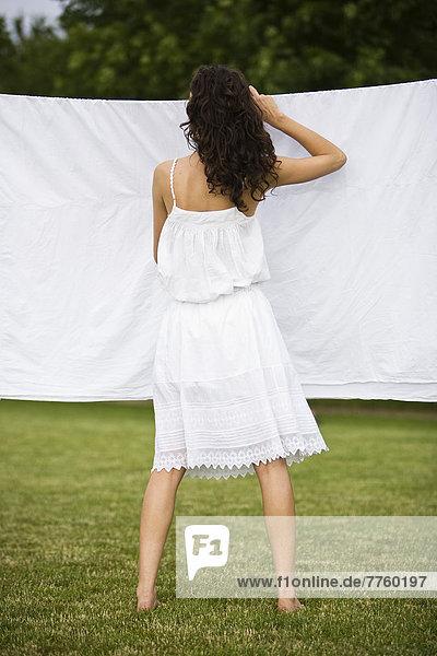 Junge Frau hängt ein weißes Laken  Oudoors