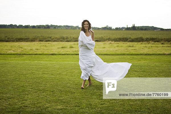 Junge Frau auf einem Feld  weißes Laken am Körper  Oudoors