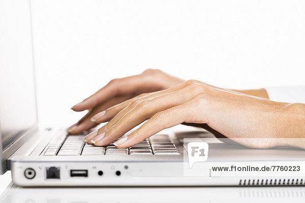 Frauenhände schreiben auf Laptop