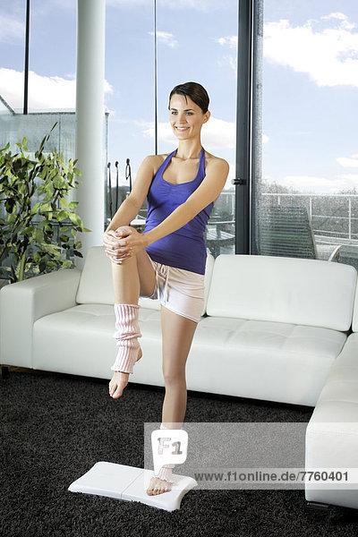 Junge Frau beim Sport mit Wii Fit