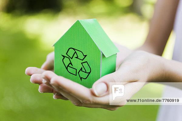 Junge Frau hält grünes Musterhaus mit Recyclingzeichen