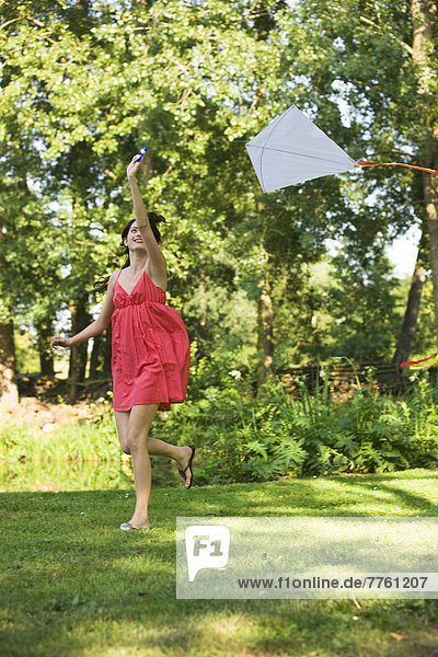 Young woman playing with kite