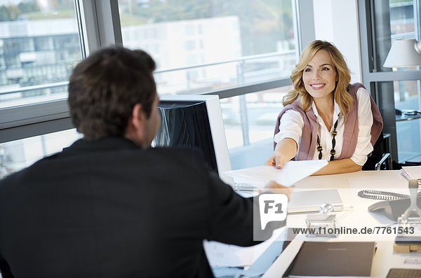 Business couple exchanging a paper in office
