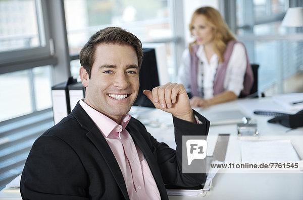 Geschäftsmann lächelt vor der Kamera  Frau im Hintergrund