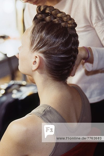 Hairdresser making hair piece to a woman sitting in profile
