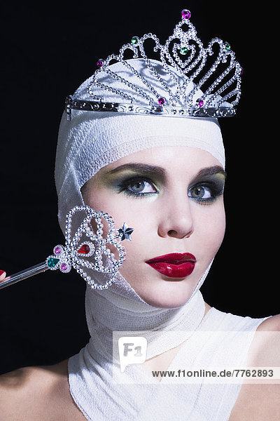 Young woman with bandages on head and breast  holding fairy wand  tiara