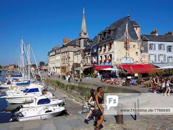 The Old Dock with pleasure boats moored  and Saint Etienne quay with cafes  church and tourists  Honfleur  Auge region  normandy  France.