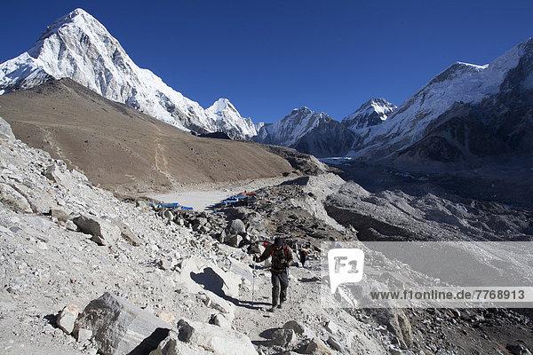 Wanderweg im Everest-Nationalpark  hinten die Ortschaft Gorak Shep und die Berge Kalar Patthar und Pumori  links  sowie der Khumbu-Gletscher  rechts