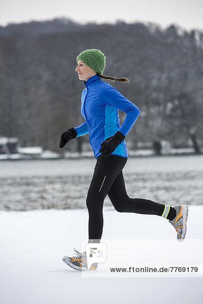 Joggerin bei einem winterlichen Lauf am Baldeneysee