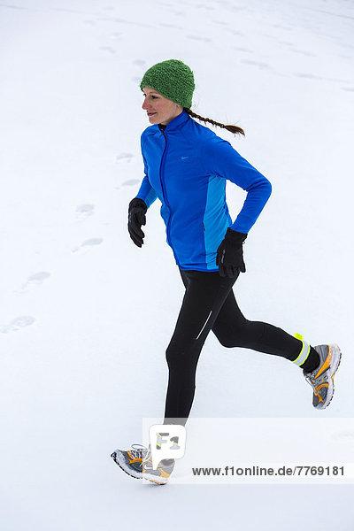 Joggerin bei einem winterlichen Lauf im Schnee