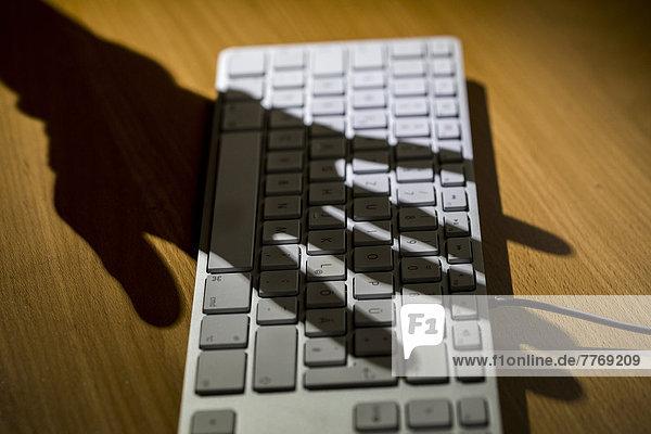 Schatten einer Hand über einer Computertastatur