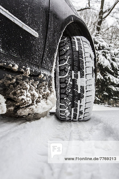 Car with winter tyres parked on a road covered with snow