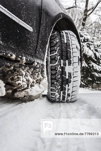 Auto mit Winterreifen steht auf einer Straße mit geschlossener Schneedecke