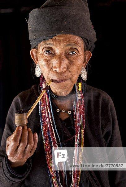 rauchen rauchend raucht qualm qualmend qualmt nahe Frau Tradition Wohnhaus Eingang Hügel bunt schwarz Dorf Myanmar Asien Kleid Shan Staat Volksstamm Stamm