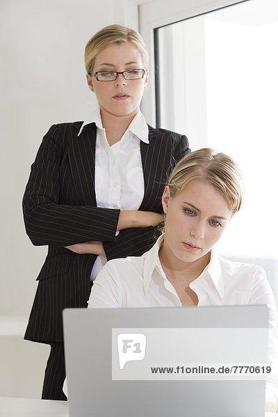 Businesswoman supervising woman using laptop computer