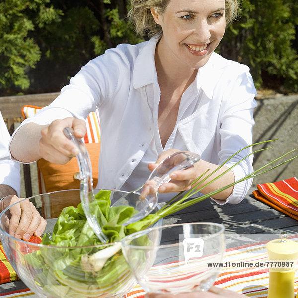 Frau mischt Salat