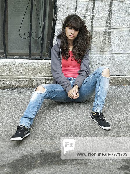 Teenage girl sitting in the street