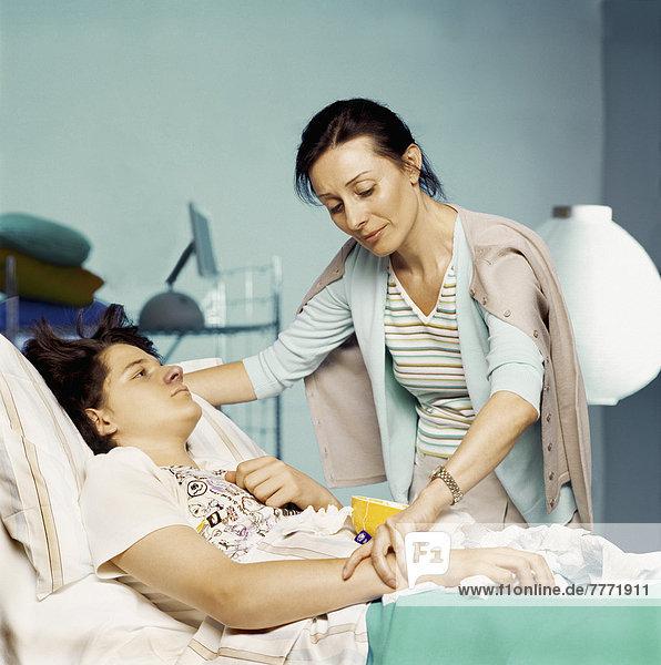 Frau  die den Puls eines Teenagers nimmt  der im Krankenhausbett liegt.