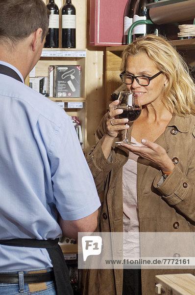 Eine abendländische Frau  die eine Flasche Wein auswählt