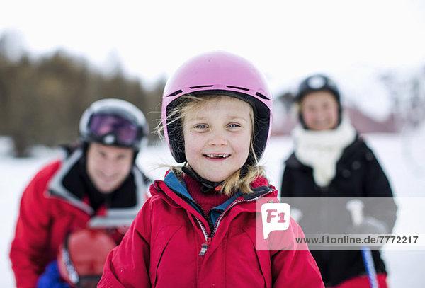 Porträt des kleinen Mädchens in Skikleidung lächelnd mit Familie im Hintergrund