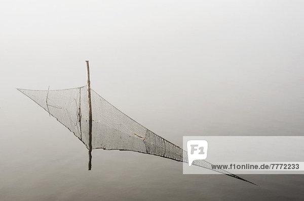 Fischernetz im nebligen See