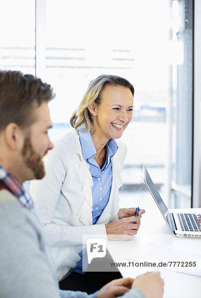 Fröhliche reife Geschäftsfrau sitzt mit Kollegen am Schreibtisch im Büro