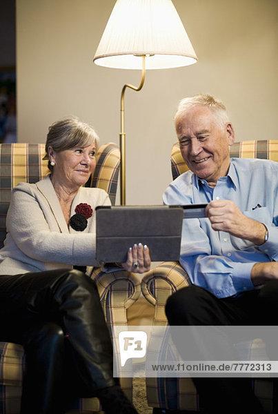 Senior Paar online einkaufen durch Kreditkarte und digitales Tablett