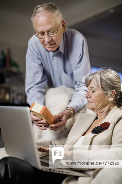 Senior Paar überprüft Produktdetails auf dem Laptop