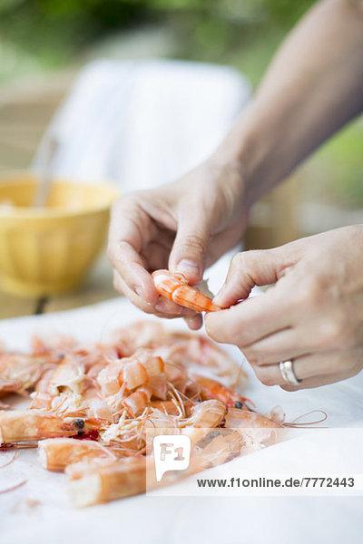 Frauenhände beim Garnelenputzen am Tisch