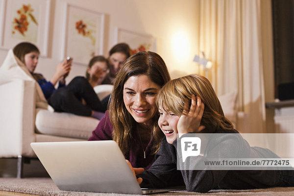 Glückliche Mutter und Sohn mit Laptop auf dem Boden mit Familie auf dem Sofa im Hintergrund