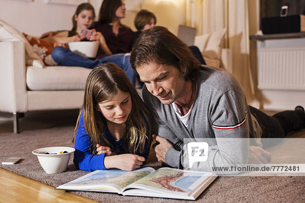 Vater und Tochter lesen Landkarte auf dem Boden mit Familie auf Sofa im Wohnzimmer