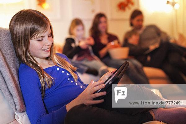 Fröhliches Mädchen mit digitalem Tablett und Familie auf dem Sofa im Wohnzimmer