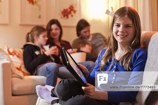 Porträt eines glücklichen Mädchens mit digitalem Tablett und Familie auf dem Sofa im Wohnzimmer
