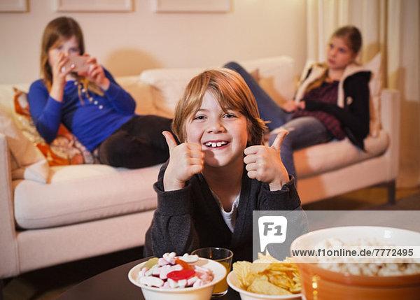 Porträt eines glücklichen Jungen mit Daumen nach oben am Couchtisch mit Schwestern im Hintergrund