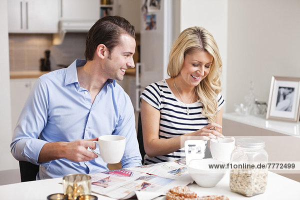 Glückliches Paar beim gemeinsamen Frühstück am Tisch