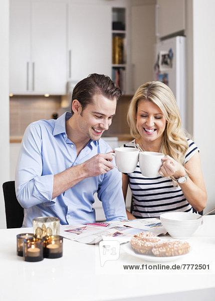 Ein glückliches Paar toastet Kaffeetassen am Frühstückstisch.