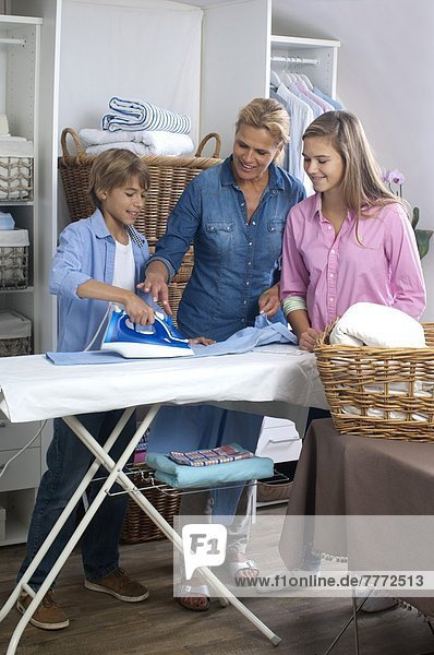 Woman ironing with her children