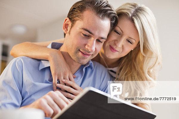Ein glückliches Paar  das gemeinsam ein digitales Tablett benutzt.