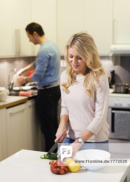 Junge Frau beim Gemüsehacken mit Mann in der Küche