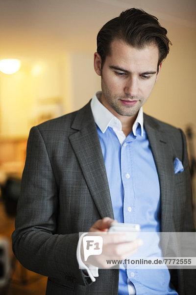 Mittlerer Erwachsener Mann im Anzug mit Handy zu Hause