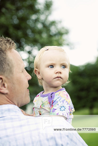 Vater trägt kleines Mädchen im Hof